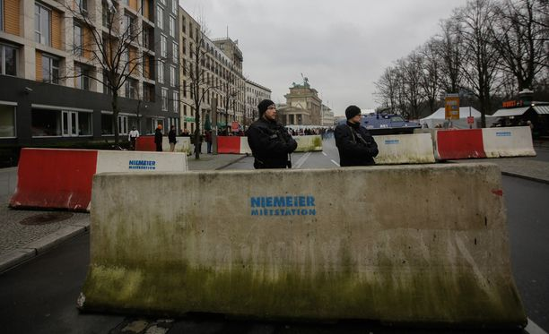 Taustalla näkyvän Brandenburgin portin aluetta suojataan uutenavuotena painavin turvatoimin.
