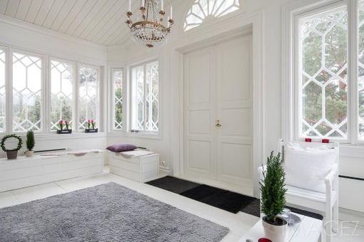 Vuonna 2012 perinteiseen tyyliin rakennetun hirsitalon lasikuisti on kookas ja komea. Isot koristeelliset ikkunat antavat valon virrata sisään.