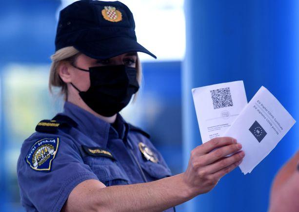 Koronapassia tarvitaan paitsi maiden sisällä, myös monien maiden rajoilla. Kuva Kroatian ja Slovenian väliseltä rajanylityspaikalta, jossa paikallinen poliisi tarkastaa koronapasseja.