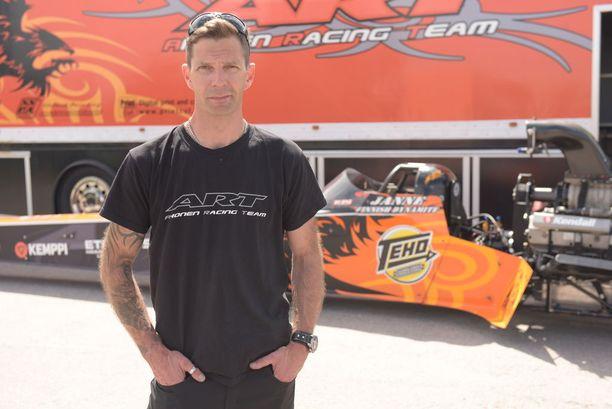 Janne Ahonen poseeraa takana olevan Top Fuel -luoka dragster-autonsa kanssa.