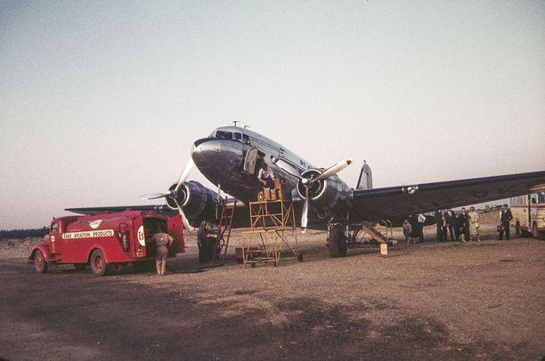 Lentokone ja matkustajia 1952 valmistuneella Helsingin lentoasemalla joskus 50-luvulla. Lentokonetta tankataan Esson autosta ja matkatavaroita lastataan koneeseen.