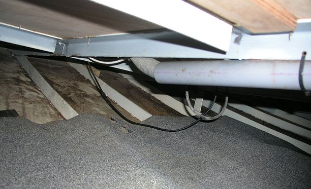 Metallisten rakennekaarien päälle on asetettu matto, jonka päällä matalaan tilaan piiloutunut ihminen on maannut.