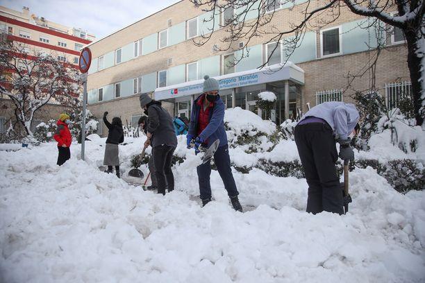 Vapaaehtoiset auttavat lumenluonnissa madridilaisen Gregorio Maranon -sairaalan edustalla sunnuntaina.