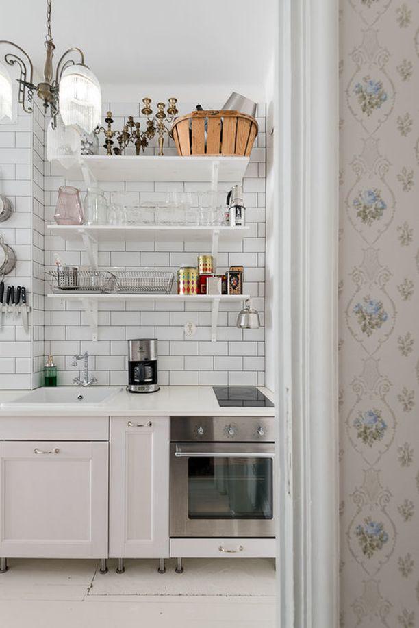 Ihanaa vanhan ajan tunnelmaa! Yläkaappien tilalle asennetut hyllyt toimivat loistavasti tässä keittiössä. Välitilan valkoinen tiililadonta kruunaa kokonaisuuden.