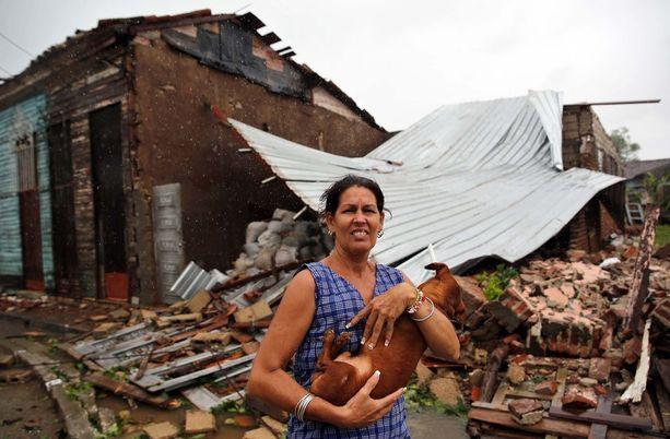 Nainen piteli koiraansa tuhoutuneen kotinsa edessä Remediosin kaupungissa Kuubassa.