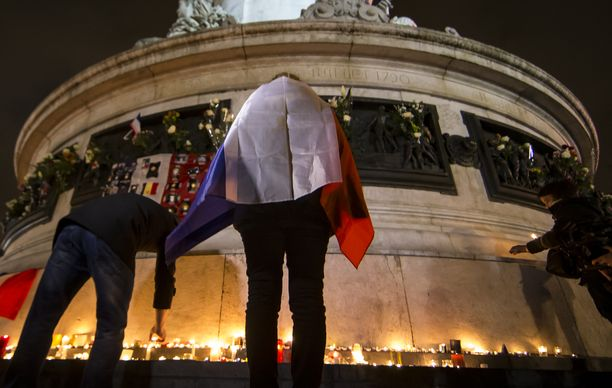 Nainen seisoi Ranskan lippuun kietoutuneena muistomerkin edessä 13. marraskuuta 2016, tasan vuosi tuhoisien iskujen jälkeen.