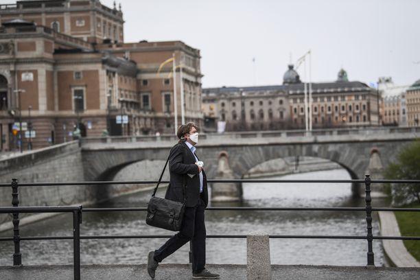 Kasvosuojaa käyttävä mies käveli Ruotsin kuninkaallisen oopperan ohi Tukholmassa 27. huhtikuuta.