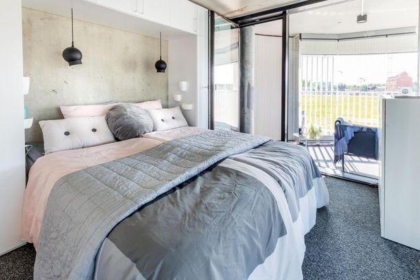 Tähän kokolattiamatolla kuorrutettuun pehmeään makuuhuoneeseen betoniseinä tuo kivan kontrastin.