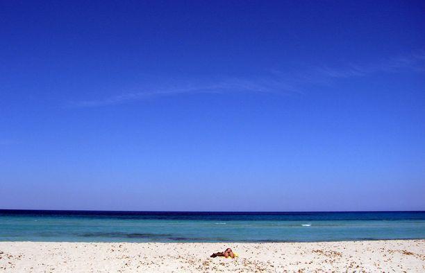Nuori nainen ottaa aurinko albanialaisella hiekkarannalla.