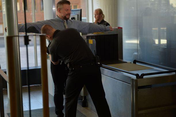 Turvatarkastaja tarkisti Jari Sillanpäätä Helsingin käräjäoikeuden aulassa keskiviikkoaamuna.