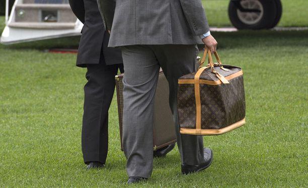 Avustajat kantoivat Trumpin perheen Louis Vuitton -merkkistä laukkua helikopteriin.