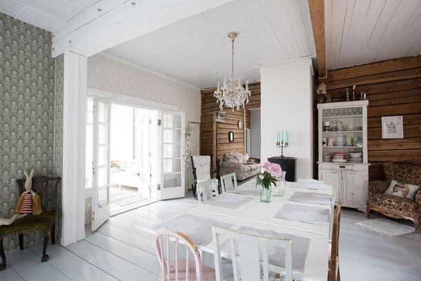 Tässä kodissa perinteisen hirsitalon ja herraskartanon tunnelmat kohtaavat toisensa. Vaaleanharmaaksi maalattu lautalattia yhdistää hienon kokonaisuuden.