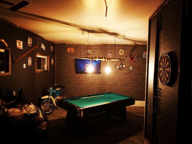 Janne Kokkosen äijäluolassa on tummat seinät ja baarimaiseen tyyliin mystinen valaistus.