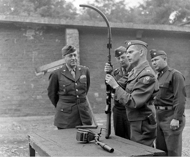 Amerikkalaissotilaat ihmettelemässä kulman taakse ampuvaa kivääriä sodan päättymisen jälkeen.