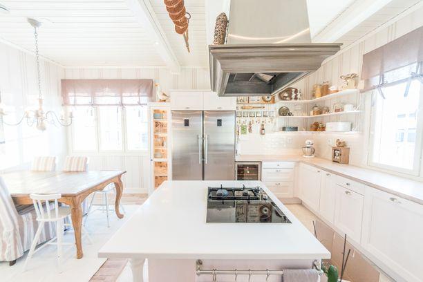 Keittiössä on raitakuosisella kankaalla päällystettyjä tuoleja, raitatapetit, mieletön saareke liesituulettimineen ja katon rajassa roikkuu leipätanko. Tässä tilassa maalaisromantiikka ja Long Island törmäävät.