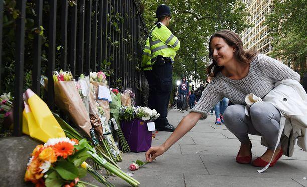 Nainen toi kukkia uhrien muistoksi Lontoon puukotuspaikalle.