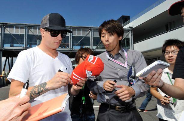 Räikkönen jakamassa nimikirjoituksia.