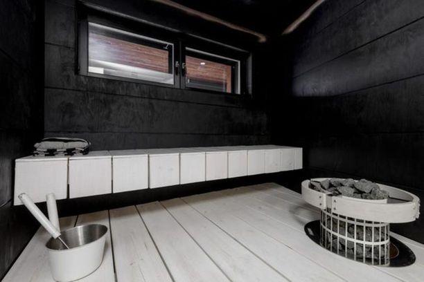 Helsinkiläisen omakotitalon saunat ovat mustaksi värjättyä uritettua vaneria ja mittatilauslauteet valkoiset. Pylväskiukaan ympärille on tehty suojakaari samasta materiaalista.