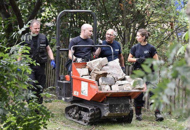 Poliisi kuljettaa puutarhatontilta betonilohkareita.