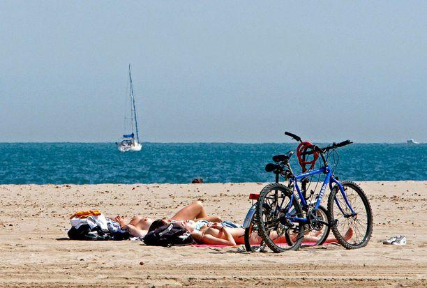 Kataloniaskylän naiset saavat nyt lekotella uima-altailla ilman yläosaa. Tässä auringonottajia Barcelonan rannoilla.