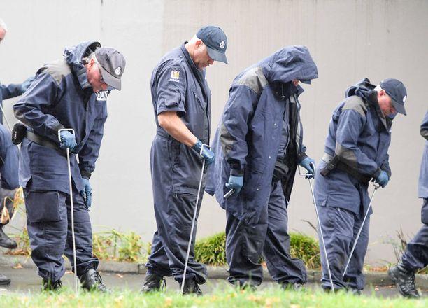 Poliisit tutkivat maastoa toisen iskun kohteeksi joutuneen moskeijan lähellä.