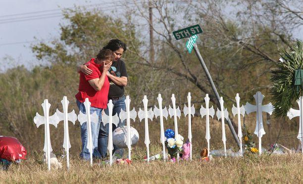 Ihmiset itkivät Texasin Sutherland Sprinsin uhrien muistoksi pystytettyjen ristien äärellä tiistaina.