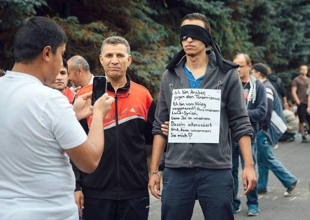 Freitalissa turvapaikkapäätöstä odottava nuori arabi kertoo julisteessaan olevansa arabi, vastustavansa terrorismia, paenneensa sotaa ja pyytävänsä hyväksyntää saksalaisilta.