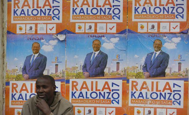 Mies istuu vaalijulisteiden peittämän seinän edustalla Nairobissa.