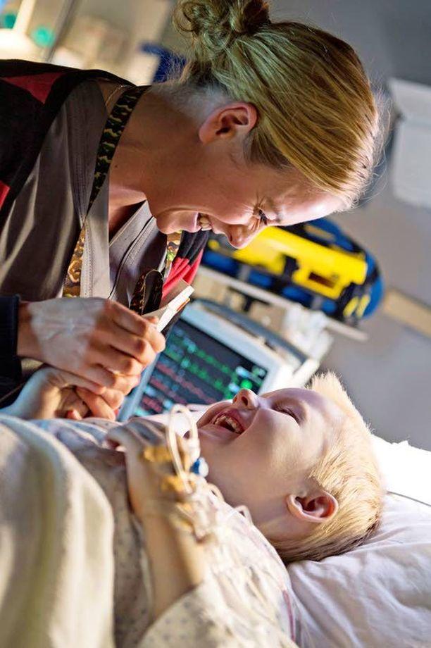 Iina Kuustonen naurattaa potilasta esittävää lasta Syke-sarjan kuvauksissa. Iiriksen näyttelemistä Kuustonen pitää palkitsevana. – On siistiä päästä tekemään kerrankin jotain ihan erilaista.