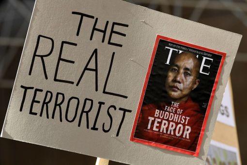 """Mielenosoittaja kantoi munkki Wirathua esittävää Time-lehden kantta Australian Melbournessa viime viikolla. Kyltin tekstissä lukee """"todellinen terroristi""""."""