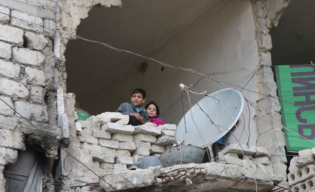 Lapset kurkistelivat ulos osittain tuhoutuneesta kodistaan viime torstaina Aleppossa.