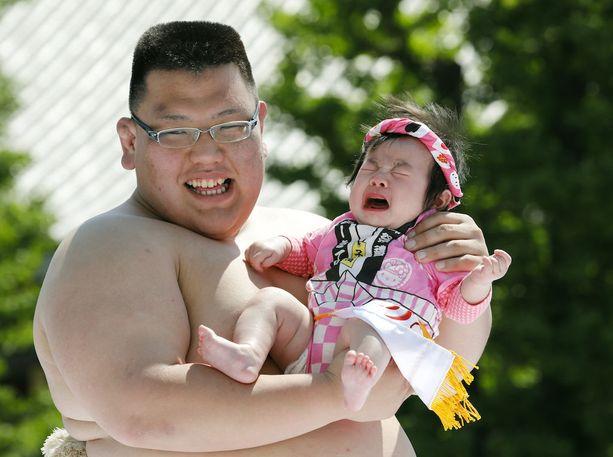 Amatöörisumopainijat pitelevät vauvoja kisan aikana.