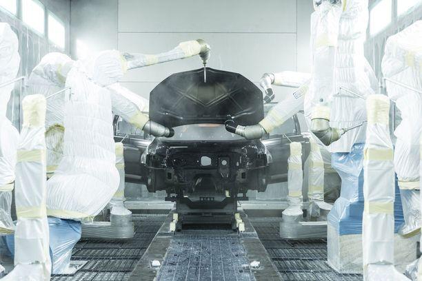 Robotti ja ihminen. Kori hitsataan ja maalataan pääosin automaattisesti, kun taas kokoonpano tehdään suurimmalta osin käsin.