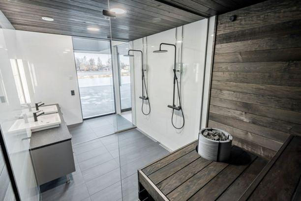 Mustat hanat jatkavat saunan tummaa ilmettä pesutiloihin. Saunasta avautuu näkymä Aurajoelle.