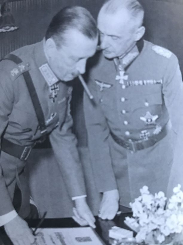 Marsalkka Mannerheim ja saksalainen yhteyskenraali Waldemar Erfurt katselevat Hitleriltä lahjaksi saatuja kunniakirjoja.