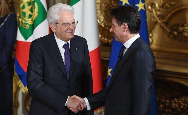 Italian presidentti Sergio Mattarella (vas.) onnittelee juuri virkavalansa vannonutta pääministeriä Giuseppe Contea.