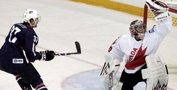 USA:n Mark Burish koettaa Kanadan maalivahti Cam Wardin taitoja.