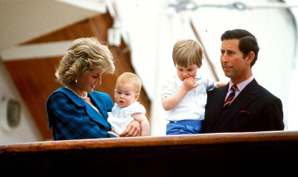 Prinsessa Dianan sylissä prinssi Harry ja prinssi Charlesin sylissä prinssi William.