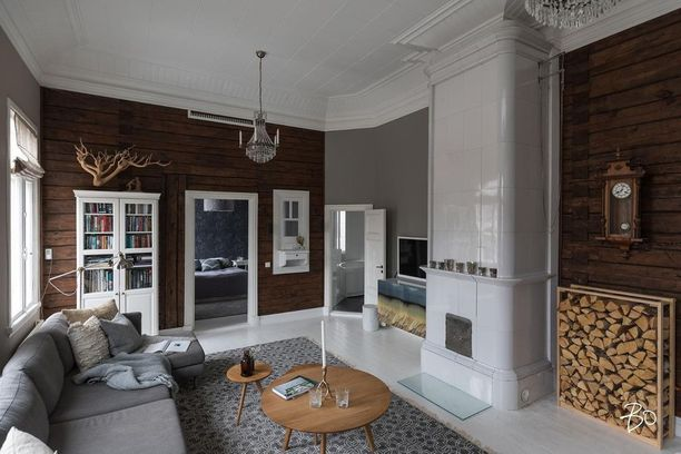 Trendikäs harmaa sohva, tummanruskea hirsiseinä ja valkoiseksi maalattu lankkulattia. Mikä seesteinen yhdistelmä! Tunnelman kruunaavat tietysti komea kakluuni, perinteinen seinäkello ja kristallikruunu.