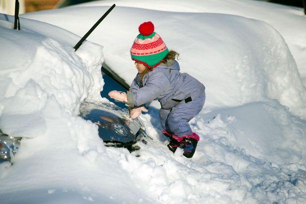 Kolme vuotias Tess Jorgensson kaivaa autoa lumesta Alexandrian kaupungissa.