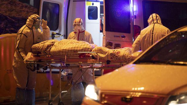 Potilasta kuljetetaan sairaalaan Wuhanissa. Koronavirukseen on toistaiseksi kuollut ainakin 25 ihmistä.