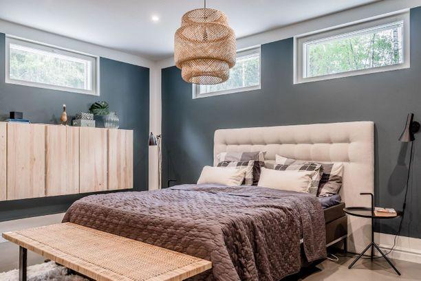 Tummanharmaat seinät ovat saaneet kylkeensä vaaleat huonekalut ja lämpimän ruskean. Vaaleaksi maalattu katto tuo tilaan avaruutta.
