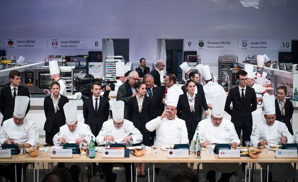 Tuomaristo arvostelemassa kokkien taidonnäytteitä.