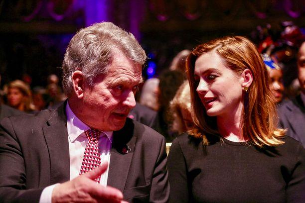 Sauli Niinistö uppoutuneena keskusteluun Anne Hathawayn kanssa.