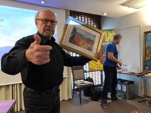 Juha Väätäinen esitteli taidettaan keskiviikkona järjestetyssä lehdistötilaisuudessa. Kädessään hänellä on vedos, kuvassa taustalla näkyy yrityksille tarjottavia originelleja maalauksia.