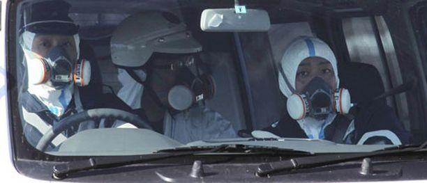 Kaasunaamarein varustautuneet poliisit partioivat Fukushiman ykkösreaktorin aluetta lauantaina.