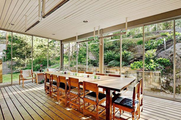 Espoolaisen omakotitalon terassilla on suuri ruokapöytä isommallekin seurueelle. Suurien ikkunoiden kautta luonto on koko ajan läsnä.