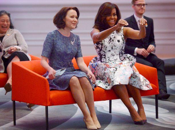 Jenni Haukio istui sinertävässä mekossaan Yhdysvaltain ensimmäisen naisen Michelle Obaman vierellä.