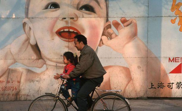 Mies kuljetti pientä tyttöä pyörällä.