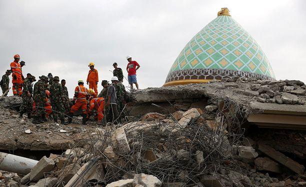 Pelastajat seisovat tuhoutuneen moskeijan katolla yrittäen etsiä raunioista selviytyjiä.
